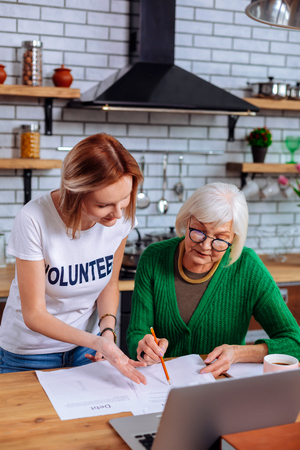 Helping with papers. Appealing focused grey-haired elderly woman wearing green knitted clothes asking young-adult short-haired slim nice lady with volunteer sign t-shirt for helping with papers
