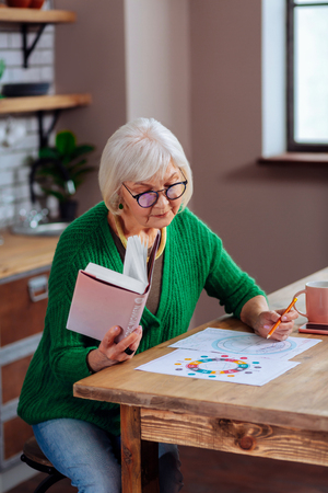 Getting the vedic tables. Aged silver-haired attractive female wearing stylish glasses and knitted emerald green apparel working on understanding the vedic tables using the vedic women book for that 스톡 콘텐츠