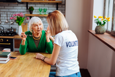 Consoling retired woman. Nice-appealing kind blonde-haired social worker in white volunteer t-shirt consoling aging upset grey-haired elegant granny in green wool cardigan.