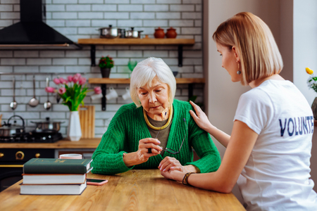 Upset grey-haired dame. Graceful wrinkled sorrowful grey-haired dame in knitted green cardigan with glasses in hands being comforted by alluring short-haired girl in white basic t-shirt.