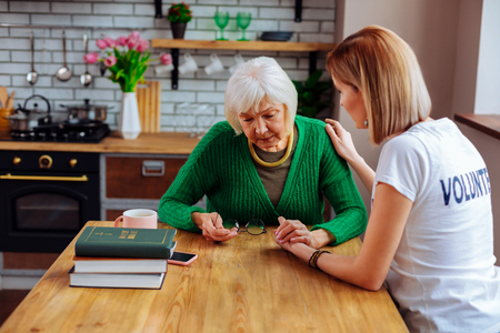 Comforting elderly woman. Young blonde short-haired woman in basic t-shirt comforting charming upset grey-haired woman in years