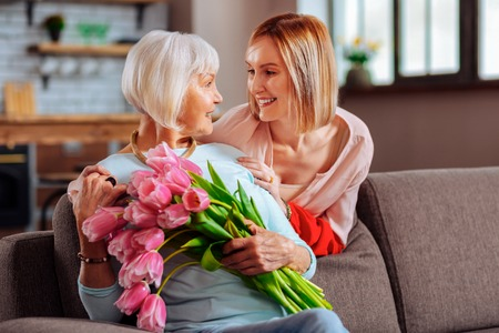 To love mother. Attractive graceful mature cheerful daughter tenderly looking at elderly sophisticated smiling mother wearing blue sweater and holding tulips Stockfoto