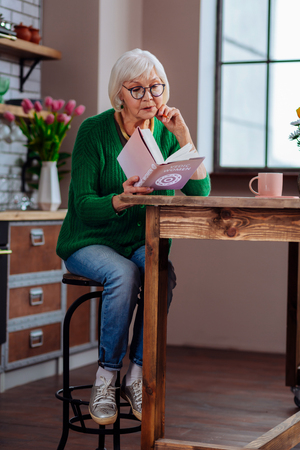 Being absorbed in book. Aging bewitching woman in smart-casual clothing and sneakers being absorbed in book sitting at modernly furnished kitchen