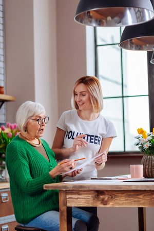 Assisting process. Graceful stylish aging woman in glasses and green knitted jumper looking surprisingly at document form while nice young blonde smiling humanitarian kindly assisting her. Фото со стока