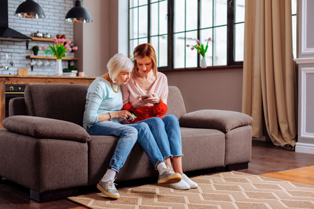 Daughter and mother spending time together. Elderly charming grey-haired female in light-blue sweatshirt and jeans sitting on sofa with her young-adult bewitching blonde daughter with phone in hands.