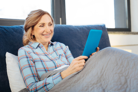 Impressed with information. Curious senior woman sitting alone in bed and looking on screen of her mobile phone