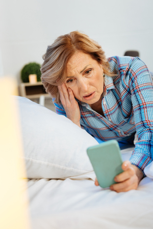Unpleasant look. Expressive light-haired woman wearing checkered pajama and inspecting smartphone while waking up Stock Photo