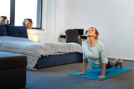 Blue yoga mat. Resolute sportive thin lady standing on her hands while training and making push-ups 免版税图像