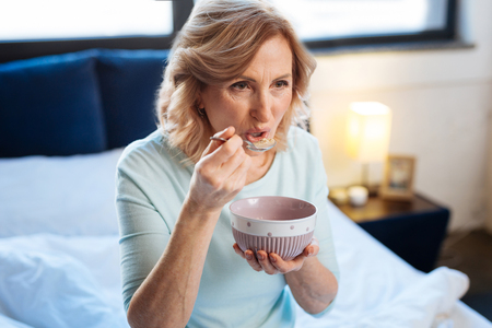 Eating morning porridge. Short-haired fit mature lady carrying metal spoon and tasting breakfast while sitting on bed