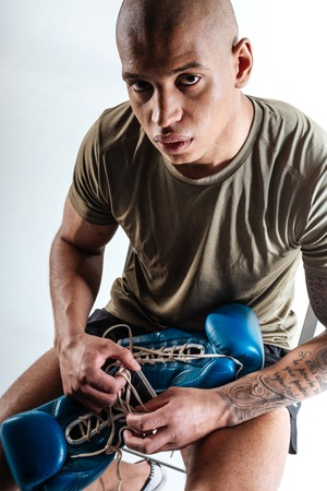 Before training. A man holding blue boxing gloves befvore training Stock Photo