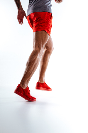Running. A mans figure wearing red shorts performing running movements Stockfoto