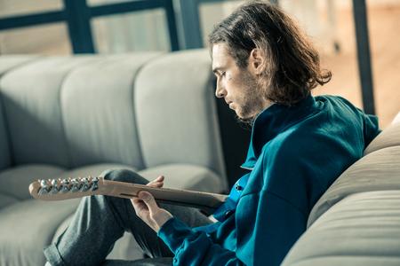 Durante la repetición diaria. Hombre de pelo oscuro concentrado con rastrojo tocando pacíficamente la guitarra mientras está solo en casa