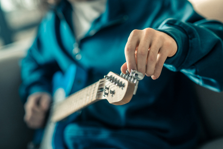 Setting up instrument. Experienced guy in blue sweatshirt pulling on strings on his electronic guitar while preparing it for repetition