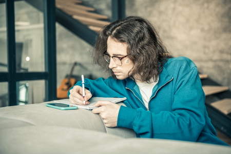 Writing down notes. Attentive long-haired guy with long hair rewriting notes in album from screen of the smartphone