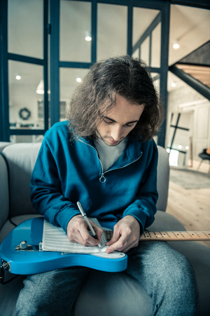 Daily repetition. Concentrated Long-haired man putting notebook on his bright guitar and writing down composition
