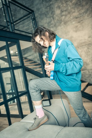 Performing with guitar. Active dark-haired professional musician in blue sweatshirt and short pants standing on sofa in stylish apartment Foto de archivo