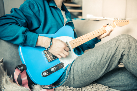 Professional instrument. Talented professional young musician resting in living room and practicing with electronic guitar