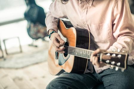 Persönliche Akustikgitarre. Erfahrener aufmerksamer Musiker, der leichtes Hemd trägt und Streicher berührt, während er sein hilfreiches Talent zeigt Standard-Bild