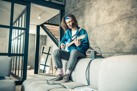 Podłączony do wzmacniacza. Stylowy, utalentowany młody chłopak ubrany w bandanę na długich włosach podczas tworzenia nowej piosenki