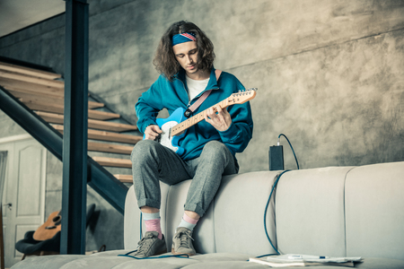 Professional guitar performing. Focused attentive guy in colorful bandana experimenting with his guitar while chilling on sofa