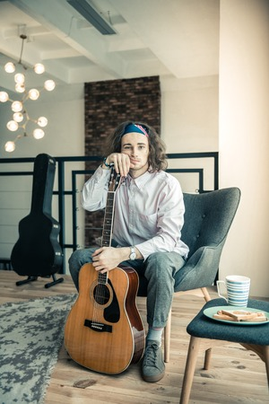 Emotional dark-haired guy. Tired upset guy with colorful bandana leaning on his guitar while sitting in armchair
