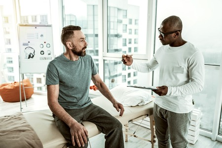 Be attentive. Concentrated male person talking to his patient, making notes