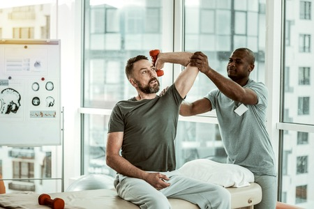 Uncomfortable pose. Conscious bearded male person lifting dumbbell while stretching his muscles