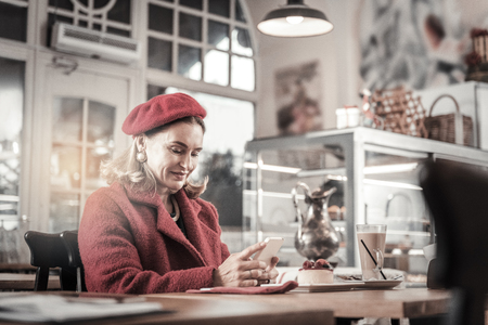 Online communication. Positive delighted lady sitting in cafe, keeping smile on her face Imagens