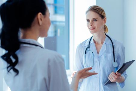 Ich habe Sie gefunden. Positiver junger Arzt mit Stethoskop um den Hals und Lächeln im Gesicht, während er in die Augen ihres Partners schaut Standard-Bild