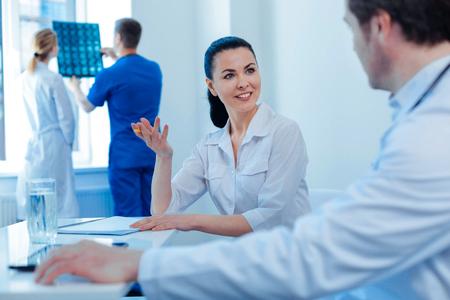 Estoy en todos los oídos. Trabajadora médica encantada manteniendo una sonrisa en su rostro y gesticulando activamente mientras consulta a su compañero de trabajo Foto de archivo