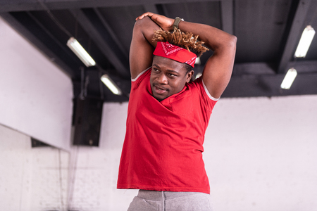 Dancing studio. Sportive dark-skinned young man stretching body before training while having stripe on head