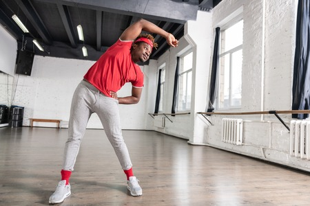 Spacious studio. Fit young man spending time in studio and warming up before dancing training
