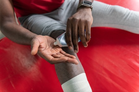 Plaster and cream. Sportive African American man squeezing healing cream on palm while treating trauma during training Stock Photo