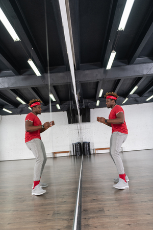 Repetition in studio. Beaming dark-haired active man having fun while dancing in front of spacious mirror