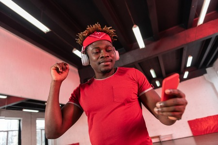 Having dancing music. Smiling short-haired guy with dreadlocks looking on smartphone screen while dancing with headphones on