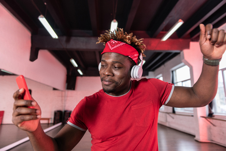 Professional headphones. Active contented young man in red t-shirt having dancing music through his headphones Stock Photo