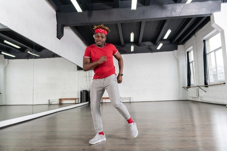 Actively dancing. Cheerful strong man with short dreadlocks being inspired while having dance repetition Stock Photo