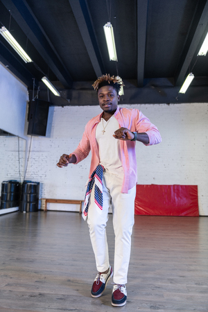 Moving around. Active young man in light outfit showing his skills in dancing while standing on wooden floor Stock Photo