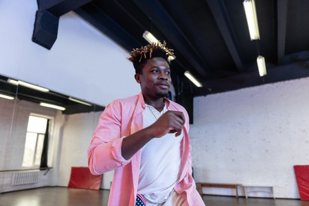 Good-looking guy. Cheerful good-looking young man with short dreadlocks wearing pink shirt while dancing in empty studio Stock Photo