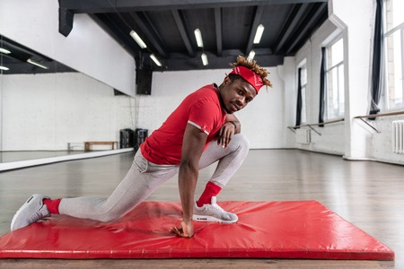 Every day routine. Strong African America young guy stretching muscles and joints while leaning on sportive mattress