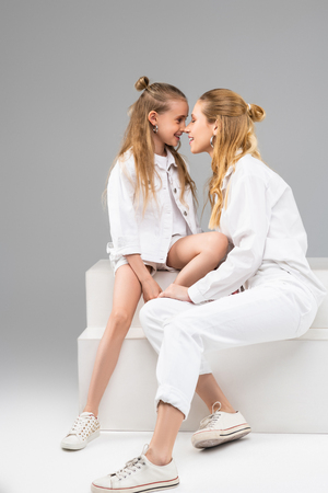 Rubbing noses. Long-haired adult girl with hair bun petting nose of her little sister while participating in photo shoot