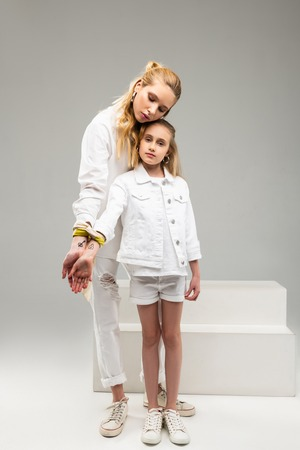 Pictures on the wrists. Long-haired peaceful woman having connection with little girl while presenting lock and key on the wrists Stock Photo
