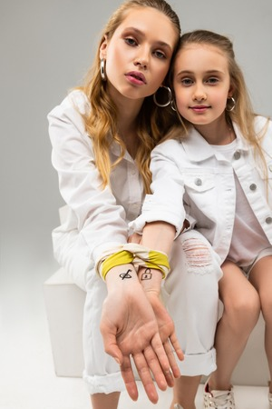 Lock and key. Pretty long-haired ladies in white outfits displaying connecting tattoos and yellow piece of fabric
