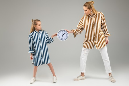 Long-haired ladies. Light-haired beautiful girls wearing bright striped shirts and pulling over round wall clock