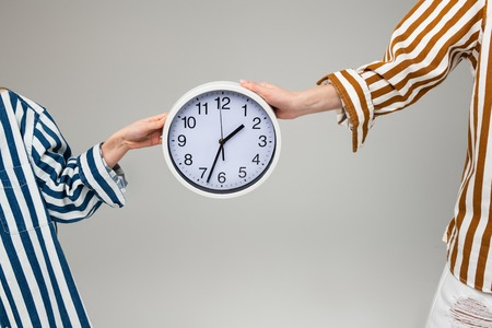 Round wall clock. Women in oversize striped outfits carrying plain wall clock between them with both hands