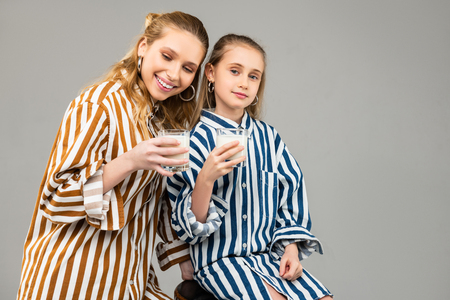 Glass with milk. Positive young ladies spending time together and drinking milk from filled glasses