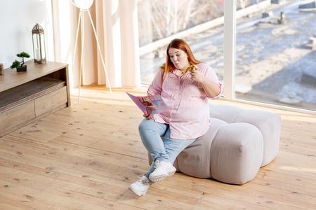 Relaks w domu. Widok z góry na pozytywną młodą kobietę czytającą magazyn o modzie podczas relaksu w domu