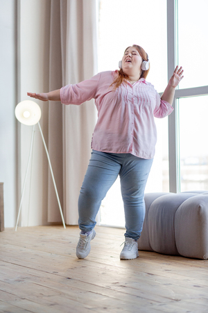 Music lover. Delighted plump woman dancing at home while enjoying her music 免版税图像