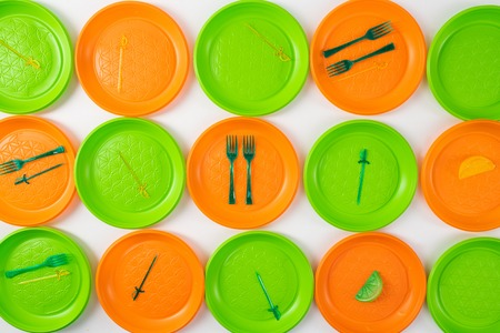 Unsystematic consumption. Disposable plastic utensils lying on bright plates as installation for anti-plastic campaign