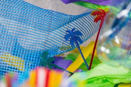 Polluting oceans. Funky colorful skewers in palm form lying on plastic blue net as installation for anti-plastic campaign
